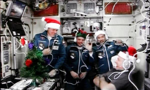 ロシアのソユーズ宇宙船から国際宇宙ステーション(ISS)に入り、サンタクロース姿で会見する野口聡一さん(右奥)=2009年12月23日、NASAテレビから