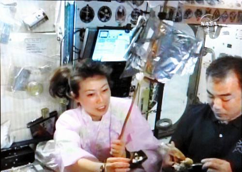 着物姿で手巻きずしをつくる山崎直子さん(左)と野口聡一さん=2010年4月15日、NASAテレビから