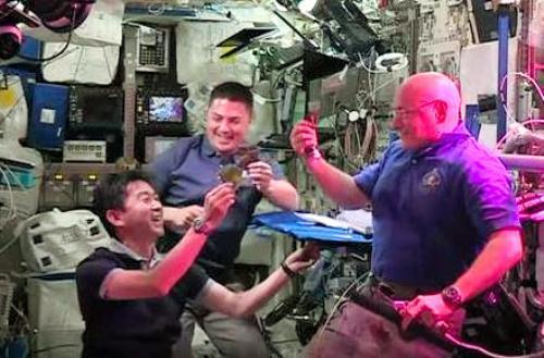 国際宇宙ステーションで栽培したレタスを同僚と試食する油井亀美也宇宙飛行士(左)=2015年8月10日、NASAの公式ツイッターから