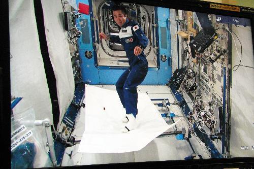 魔法のじゅうたんに見立てたシートに乗る若田さん=2009年5月15日、宇宙機構提供の中継画像から撮影