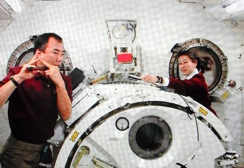 横笛で「さくらさくら」を演奏する野口聡一さん(左)と山崎直子さん=2010年4月12日、NASAテレビから