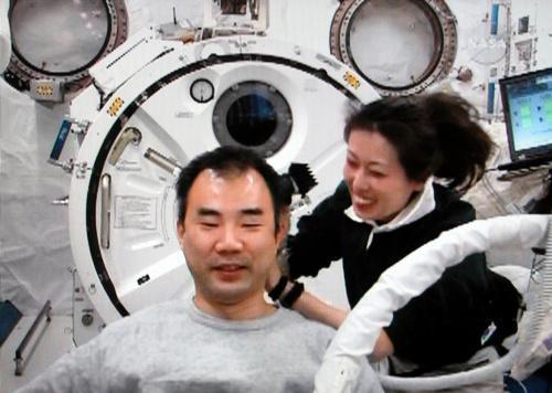 野口聡一さん(左)の頭を整髪する山崎直子さん=2010年4月17日、NASAテレビから