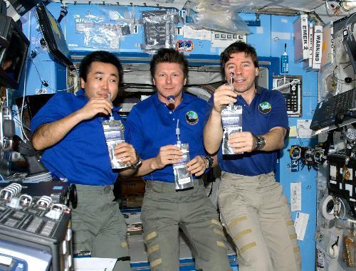 再生水を手に乾杯する若田さんらISSの乗組員たち=2009年5月20日、NASA提供