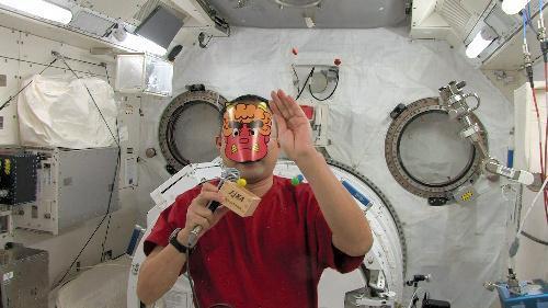 赤鬼のお面をかぶり、「豆まき」をする野口さん=2010年2月2日、NASA、宇宙機構提供