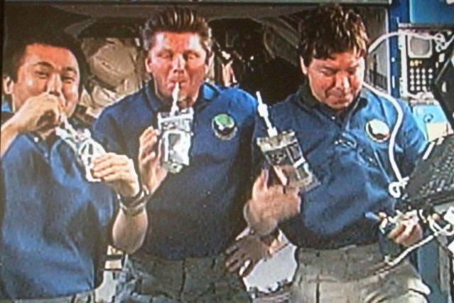 尿から作った水を飲む宇宙飛行士の若田光一さん(左端)ら=NASAテレビから、JAXA提供