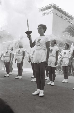 【1964年9月】聖火リレーでトーチを持つ女性走者=長崎市