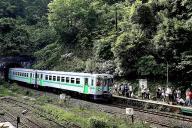 JR室蘭線の小幌駅に到着する普通列車。ホームにはたくさんの観光客の姿がある=8月13日、北海道豊浦町、山本裕之撮影