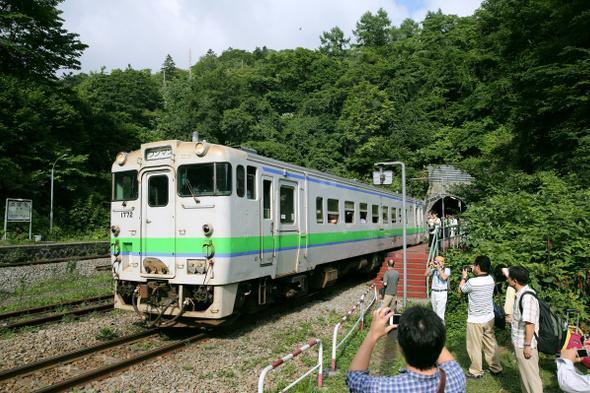 JR室蘭線の小幌駅を出発する列車を、たくさんの観光客が見つめた=8月13日、北海道豊浦町、山本裕之撮影