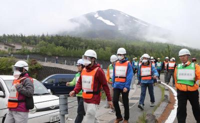 富士山噴火避難訓練。合同訓練でヘルメットやマスクをして避難する参加者たち=2015年6月11日、山梨県鳴沢村、河合博司撮影