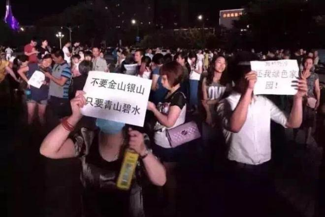 天津での爆発事故を受け、浙江省嘉興市で起きた工場建設の反対運動。政府関係の庁舎の前で「金山銀山よりも、緑を返せ」と書かれたメッセージを掲げている