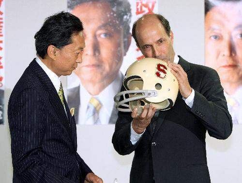 ジョン・ルース前駐日米大使。会談前、共に学んだことのあるスタンフォード大のマークが入ったアメリカンフットボールのヘルメットを手に民主党の鳩山代表(当時)と談笑。シリコンバレーにあるIT企業の合併・買収やベンチャー企業育成を手がける=2009年9月3日