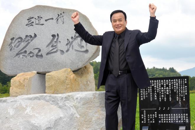 生家跡に建てられた碑の上に立つ細川たかしさん=2015年8月22日