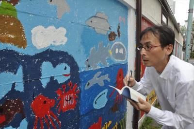 街角で見つけた壁の絵を見ながら、五輪エンブレム問題について考える中川淳一郎氏