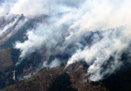 群馬の山火事。煙を上げる山林=2014年4月16日、群馬県桐生市