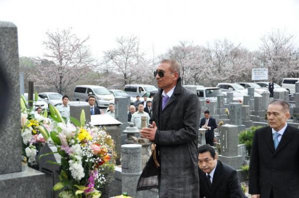 刑期満了で出所後、その足で山口組三代目田岡一雄組長の墓に参る篠田建市組長(中央)。かぶっていた帽子を取り、手を合わせた=2011年4月9日、神戸市灘区