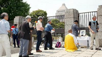 樺美智子さんの遺影が置かれた献花台に、花を手向ける参列者ら=2015年6月15日