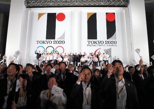 東京五輪・パラリンピックのエンブレム発表を見守り、記念撮影する参加者ら=2015年7月24日、東京都新宿区の東京都庁、林敏行撮影
