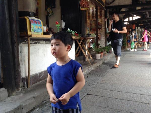 萌えヘアピンを付けた少年=中国・浙江省の観光地、西塘古鎮