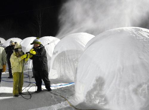 しばれ婚活。バルーンマンションに水を吹き付ける女性参加者ら。厳しい寒さの中、「楽しい」の声も=2015年2月5日、北海道陸別町