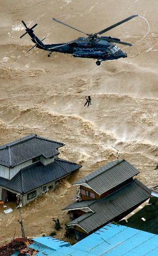 鬼怒川の堤防が決壊し、自衛隊ヘリなどが孤立した住民を次々と救助した=2015年9月10日、茨城県常総市、本社ヘリから、岩下毅撮影