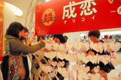 成田空港のハート形モニュメントで、旅立ちの前に恋愛祈願をする女性