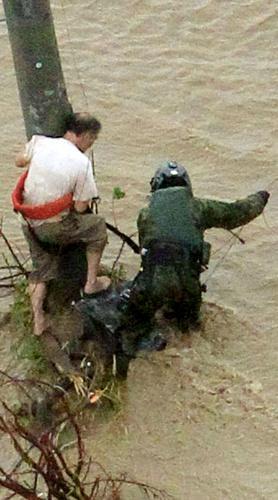 濁流の中、電柱にしがみつく男性(左)を救出する自衛隊員=2015年9月10日、茨城県常総市、本社ヘリから、岩下毅撮影