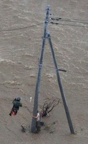 濁流の中、電柱にしがみつく男性に近づく自衛隊員(左)=2015年9月10日、茨城県常総市、本社ヘリから、岩下毅撮影