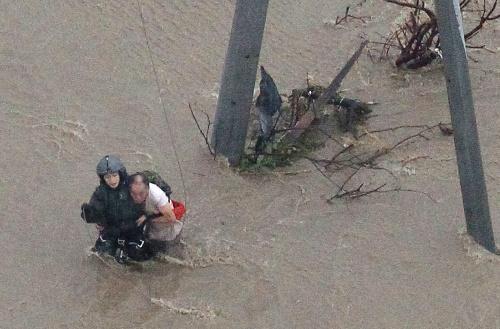 自衛隊員に抱きかかえられ、電柱から移動する男性=2015年9月10日、茨城県常総市、本社ヘリから、岩下毅撮影