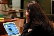 カフェでフェイスブックのお見合いサイトをチェックする女性