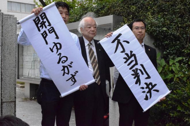 福岡高裁で開門が認められず、「不当判決」と掲げた弁護団。別の裁判で開門が確定しているので、「開門ゆるがず」の旗が並んだ=7日、福岡市、山野健太郎撮影
