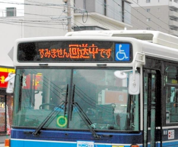 「すみません回送中です」と表示しながら停留所を通過する宮崎交通のバス=宮崎市