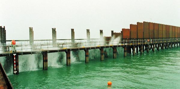 潮受け堤防建設へ向け、諫早湾を閉め切る鋼板が次々と海に落とされた。「ギロチン」と呼ばれ、干潟保全の運動に拍車をかけた=1997年、長崎県諫早市