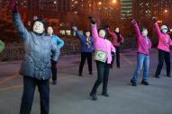 夜の駐車場で踊る広場舞のグループ。周囲には多くのマンションが立ち並ぶ=2015年1月25日、山東省・済南市、延与光貞撮影