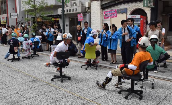 沿道の声援を受け、横向きや後ろ向きに疾走する「いす―1グランプリ」の参加者=福山市