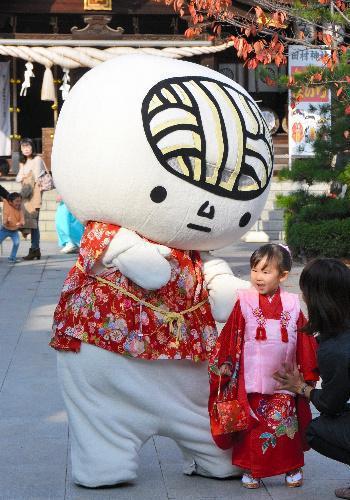 七五三参りの子どもと記念写真におさまる「うどん脳」=高松市一宮町