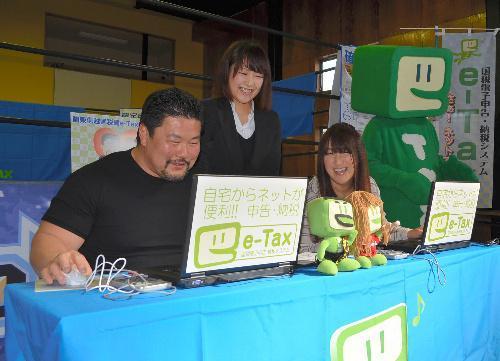 パソコンを使った確定申告を体験する佐々木健介さん(左)と北斗晶さん(右)=2014 年2月17日、埼玉県吉川市