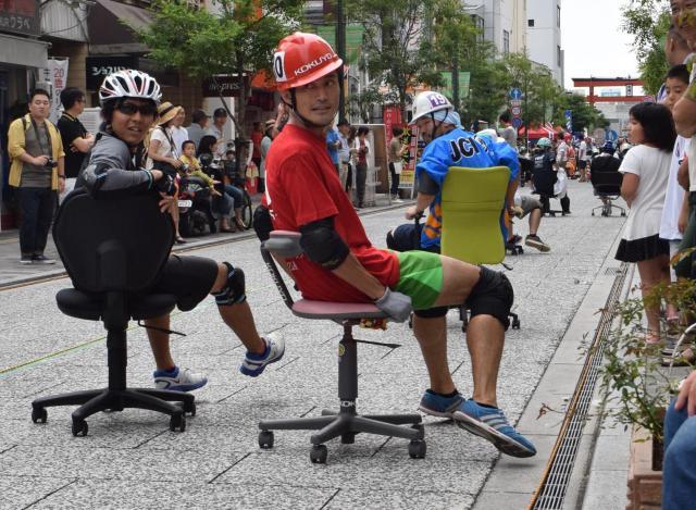 横向きや後ろ向きになって疾走する「いす―1グランプリ」の参加者=福山市