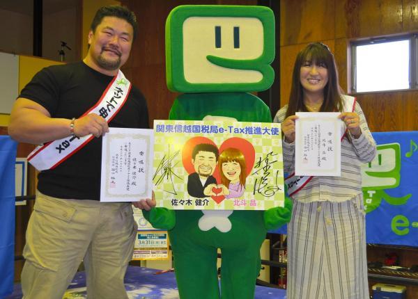 「e-Tax推進大使」の委嘱状を手にする佐々木健介さん(左)と北斗晶さん=2014年2月17日、埼玉県吉川市