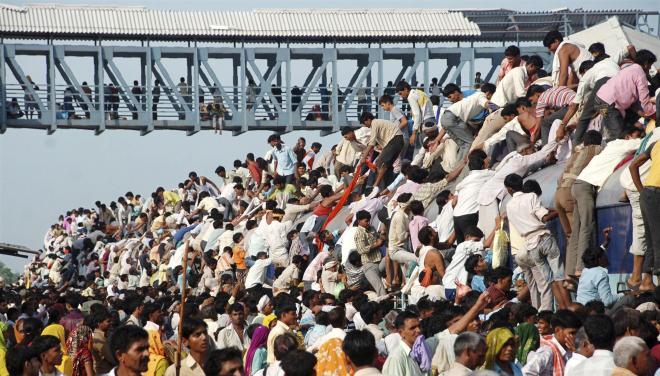 列車に乗ろうとするインドの人々=2010年、ロイター
