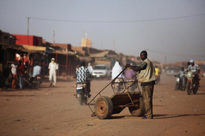 手押し車を押すニジェールの男性=2014年、ロイター