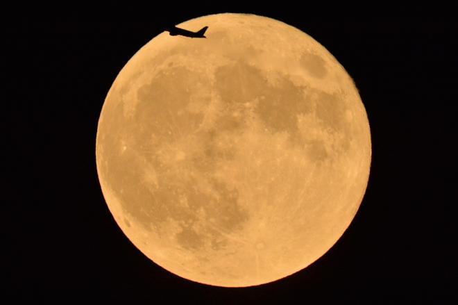 都心から見えた満月。飛行機のシルエットが浮かんだ=2015年9月28日、東京都中央区、仙波理撮影