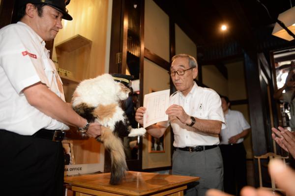 2015年8月11日 小嶋光信和歌山電鉄社長(右)から貴志駅のたまⅡ世駅長就任の辞令を受けるニタマ
