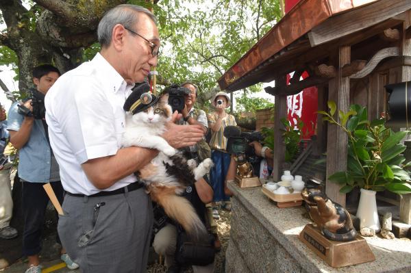 2015年8月11日 たま神社を参拝する貴志駅のたまⅡ世駅長と小嶋光信和歌山電鉄社長