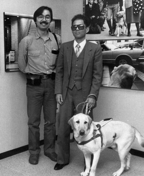 写真家の秋元良平さん(左)。右は渡辺満さんと盲導犬クイール=1989年11月