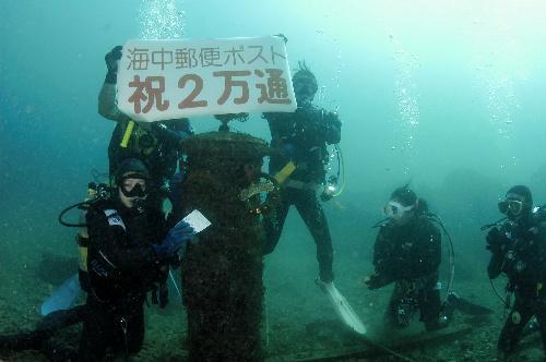 2万通目を投函するダイバーたち=2005年12月、すさみ町周参見沖で、ノアすさみ提供
