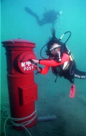 海中に設置されたポストに、はがきを入れる地元ダイビングショップのスタッフ=1999年4月