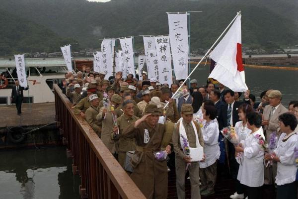 復元された桟橋で引き揚げ風景を再現してみせる体験者ら=1994年5月