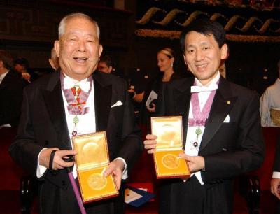 ノーベル賞授賞式を終え、メダルを手に笑顔を見せる物理学賞の小柴昌俊さん(左)と化学賞の田中耕一さん=2002年12月10日、代表撮影