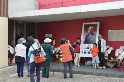 連休の初日、家族連れでにぎわう韮崎大村美術館。大村智さんの写真パネル前で記念撮影する人も=2015年10月10日