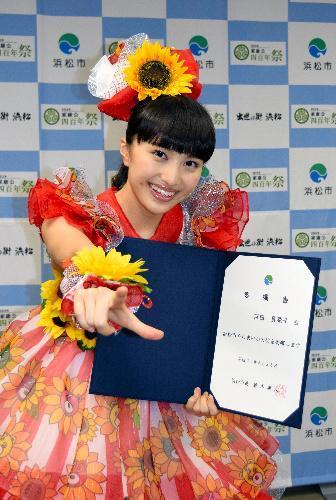 浜松市やらまいか大使の委嘱書を手に得意の決めポーズをする「ももいろクローバーZ」の百田夏菜子さん=2014年6月25日